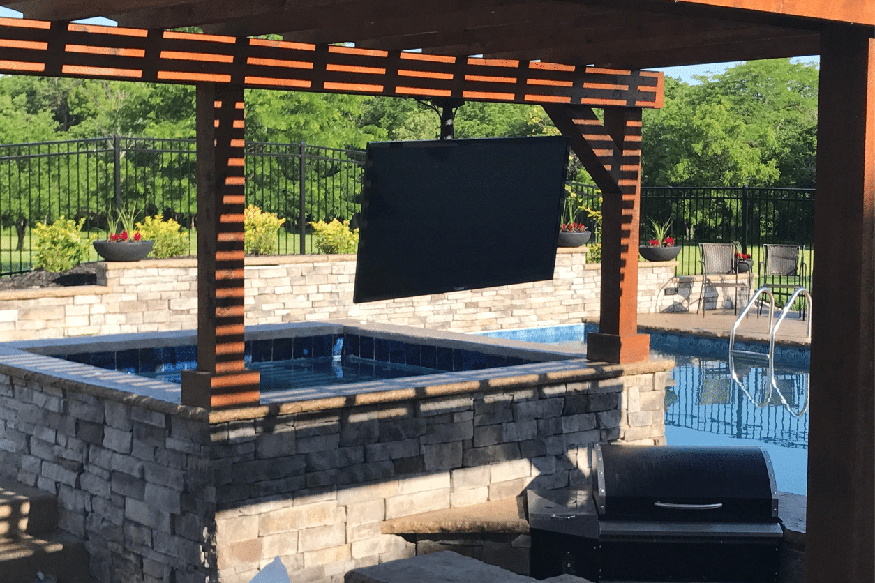 TV mounted in backyard above pool.