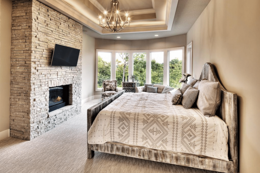 Bedroom with mounted tv above fireplace.