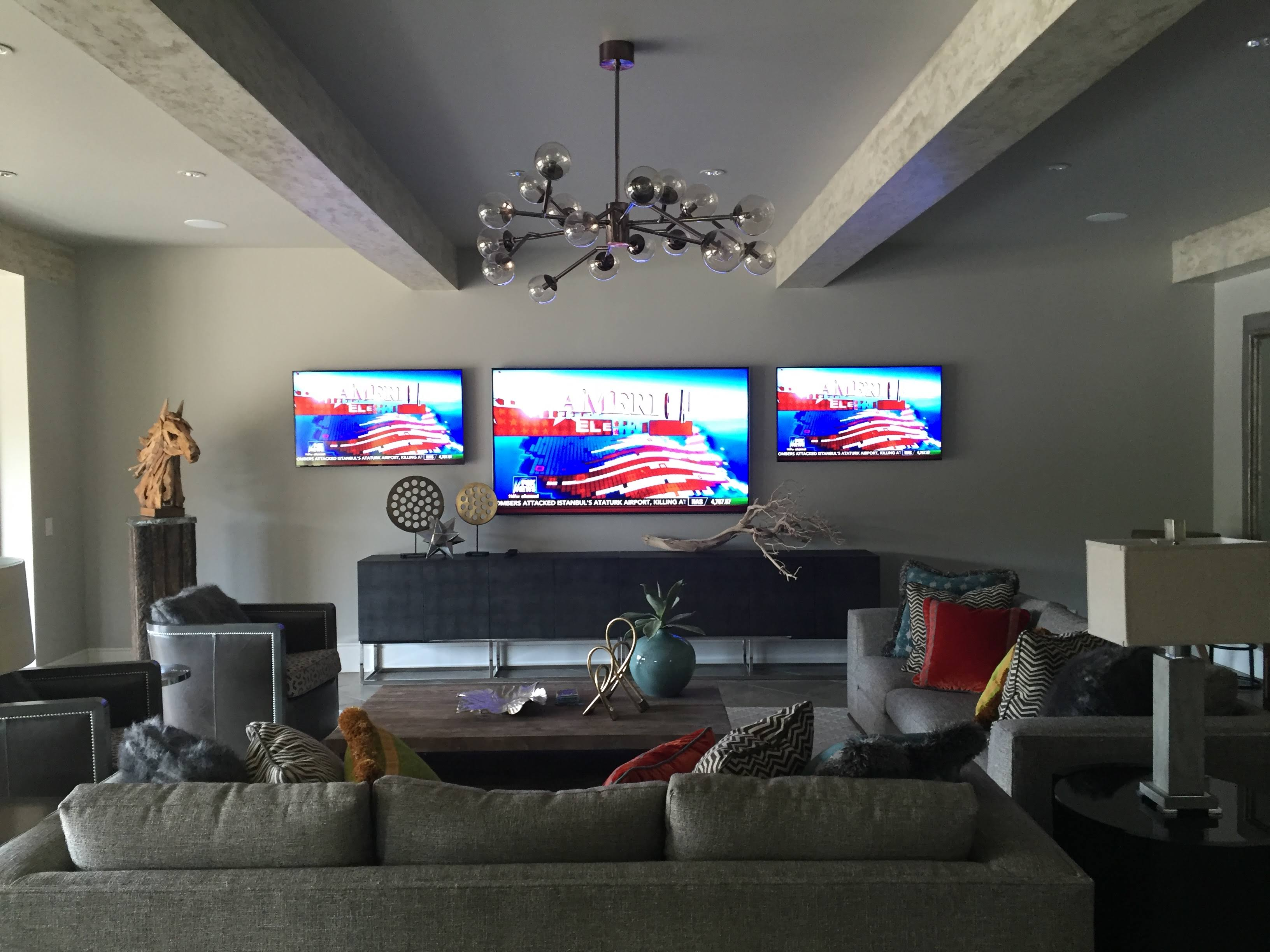 three tv screens in a living room